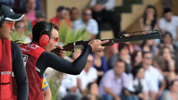 Nathan Lee Xuereb takes aim during the Malta International Double Trap Grand Prix in Bidnija as team-mate William Chetcuti looks on. The 15-year-old grabbed the headlines yesterday when he fired an extraordinary perfect score of 50 in the final barrage to win the title ahead of world class shooters Daniele Di Spigno, of Italy, and Sweden's Hakan Dahlby. Mr Chetcuti, Malta's best hope of a medal in the London Olympics, shared fourth spot with Italy's Antonio Barilla. Picture: Jason Borg