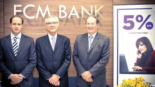 Tim Babich, John Soler and Ron Huggett commemorating FCM Bank's first-year anniversary.