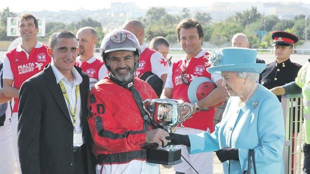Royal In driver Marco Debono (centre) receives the trophy from Queen Elizabeth. Photo: Mike Orland