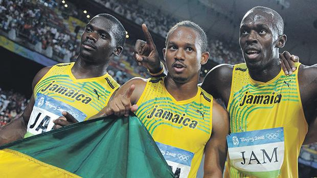 Usain Bolt (right) poses with Michael Frater (centre) and Nesta Carter.
