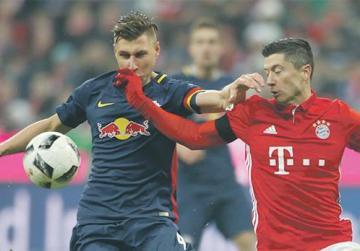 Bayern striker Robert Lewandowski (right) tussles for the ball with Willi Orban, of Leipzig.
