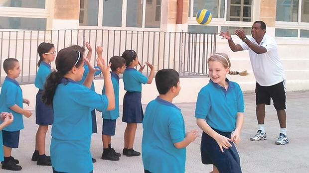 Young students during a volleyball exercise.