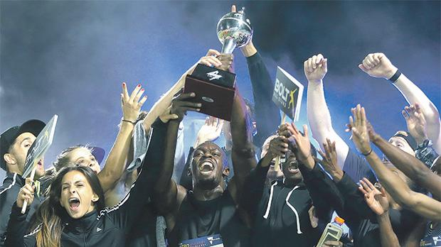 Jamaican sprinter Usain Bolt (centre) lifts the Nitro Series trophy in Melbourne yesterday.