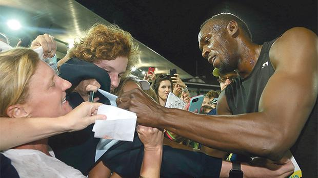 Usain Bolt signs autographs to his fans during the Nitro Serieas in Melbourne, yesterday.