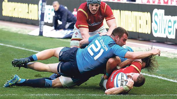 Liam Williams, of Wales, tackled by Italy's Giorgio Bronzini at the Olympic Stadium.