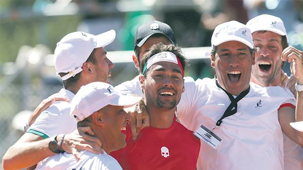 Fabio Fognini (centre) is mobbed by his Italy team-mates after winning the decider against Argentina.