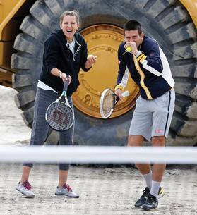 Novak Djokovic and Victoria Azarenka laugh after hitting a ceremonial serve towards onlookers and photographers during a ground-breaking ceremony for the expansion of the Indian Wells Tennis Garden.