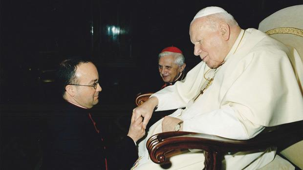 With Pope John Paul II as the then Cardinal Joseph Ratzinger looks on.