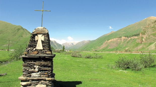 A cross adorns lush countryside.