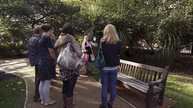 Guide Viv shows tourists the bench where she used to sleep. Photo: AFP