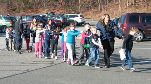 Connecticut State Police leading children from the Sandy Hook Elementary School in Newtown, Connecticut, following the shooting there yesterday. Photo: AP