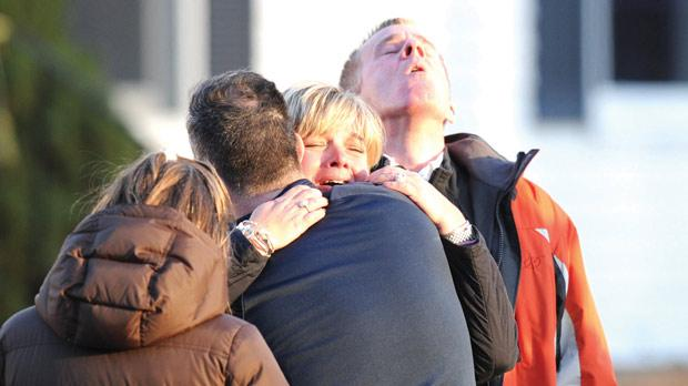 Families embrace at the aftermath of a school shooting by a lone gunman at a Connecticut elementary school. Photos: AFP
