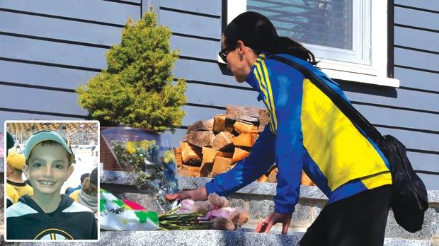 Boston Marathon runner Megan Cloke leaves flowers on the doorstep of eight-year-old Martin Richard's home in the Dorchester neighbourhood of the Massachusetts city yesterday. News reports say that Martin Richard (inset) was one of the victims of two explosions that hit the marathon as runners crossed the finish line on Monday, killing at least three people and injuring more than 100 others. Photo: Brian Snyder/Reuters