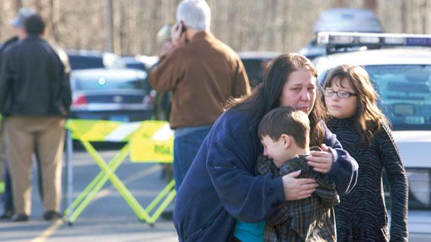 A young boy is comforted outside Sandy Hook Elementary School in Newton, in Connecticut, US, yesterday after a heavily armed gunman shot a number of students and staff there. Photo: Reuters