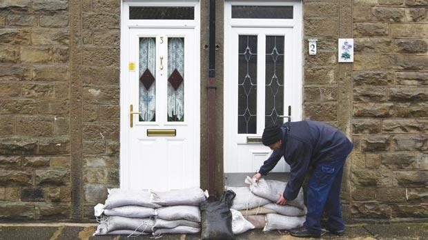 A caretaker at Green Vale Homes, placing sandbags outside homes in Whitworth, Rochdale, yesterday.