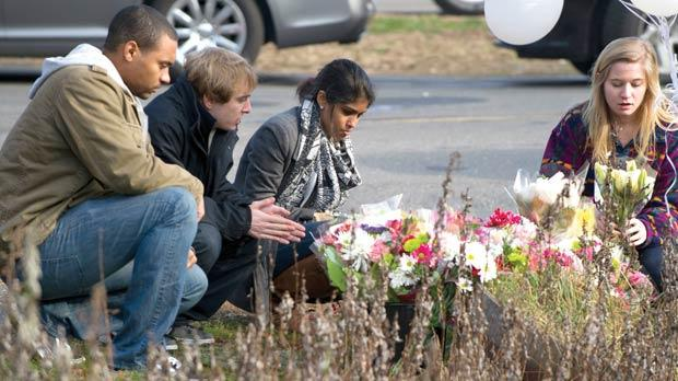 Young people leave flowers near Sandy Hook Elementary School yesterday in Newtown, Connecticut. Residents were reeling in horror from the massacre of 20 small children and six adults in one of the worst school shootings in US history. The heavily armed gunman shot dead 18 children inside Sandy Hook Elementary School. Two more died of their wounds in hospital. Photo: Don Emmert/AFP