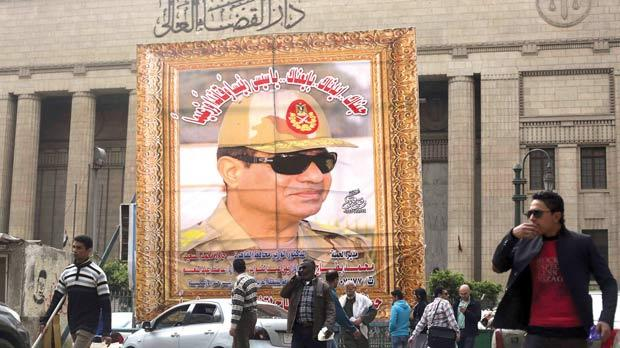 People walking past a huge banner for Egypt's army chief, Field Marshal Abdel Fattah al-Sisi, in front of the High Court of Justice in downtown Cairo, yesterday. Photo: Reuters