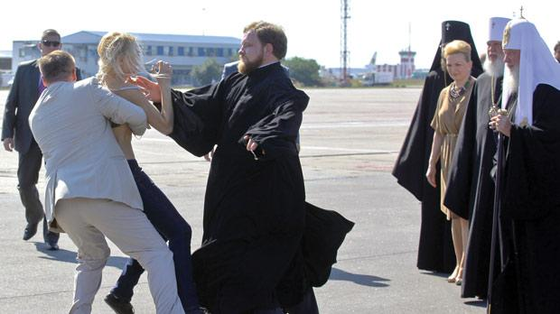 A topless activist of Ukraine women's movement Femen protesting against the visit of Russian Orthodox Church Patriarch Kirill (right) upon his arrival at the airport in Kiev, Ukraine, yesterday.
