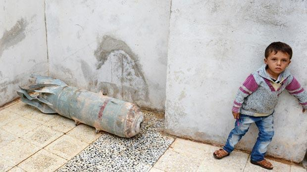 A Syrian child stands next to a deactivated bomb in his house, in the northern Syrian town of Taftanaz, in the Idlib province. Photo: AFP