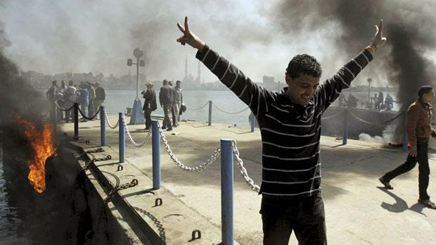 An Egyptian flashes the victory sign after several protesters set fire to tires on the city's dock in an attempt to prevent ships from coming in to Port Said at the Mediterranean end of the Suez Canal, in Egypt, yesterday. Photo: PA