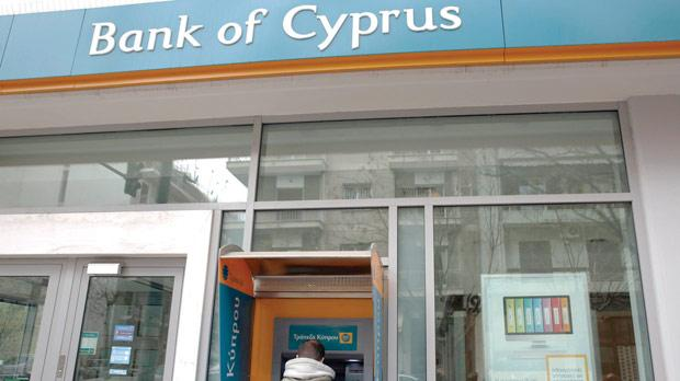 A man withdraws money from an automatic teller machine at a branch of Bank of Cyprus in Athens. Photo: Reuters