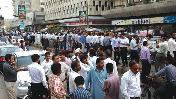 People stand outside of their office buildings following an earthquake tremor in Karachi, Pakistan, yesterday. Photo: Reuters