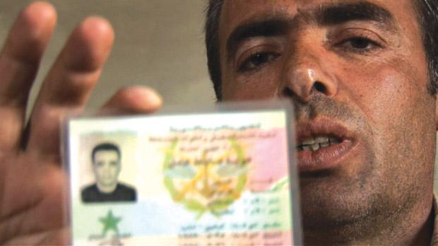 Syrian Lieutenant Colonel Hussein Harmush holding his army ID card during an interview with AFP on June 14. Photo: AFP/TV