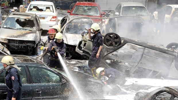 Firemen spraying cars as they extinguished fires that broke out at the scene of two huge bomb explosions outside the Palace of Justice in central Damascus yesterday.