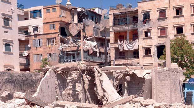 Damaged buildings after an exchange of fire between Free Syrian Army fighters and regime forces in the Seif El Dawla neighbourhood of Aleppo, yesterday.