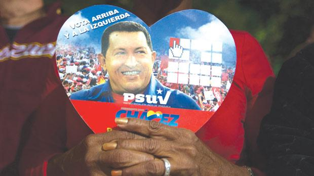A supporter of Venezuelan President Hugo Chavez holds a picture of him, as she attends a ceremony in Caracas. Photo: Reuters