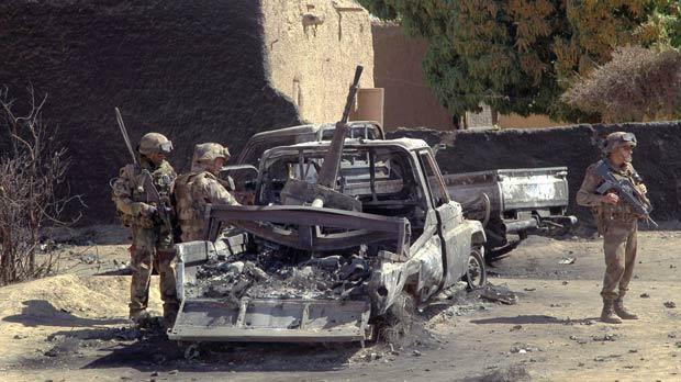 French troops inspect the charred remains of military vehicles used by radical Islamists on the outskirt of Diabaly, Mali, some 460 kilometres north of the capital Bamako,­ yesterday. Photo: AP