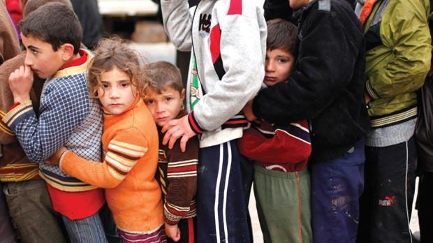 Syrian refugee children queue as they wait to receive aid from Turkish humanitarian agencies at Bab al-Salam refugee camp in Syria near the Turkish border yesterday.