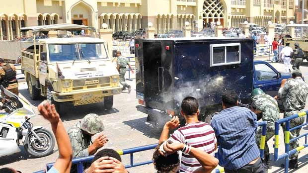Egyptians throwing stones at a police convoy carrying ex-interior minister Habib Adli outside a court in Cairo, yesterday, as hundreds of Egyptians angry with the delays in his trial clashed with anti-riot police. Photo: AFP