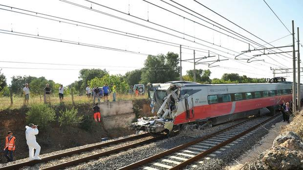 Rescuers work on the site of a collision between the truck and train in the southern city of Cisternino, yesterday. Photo: AFP
