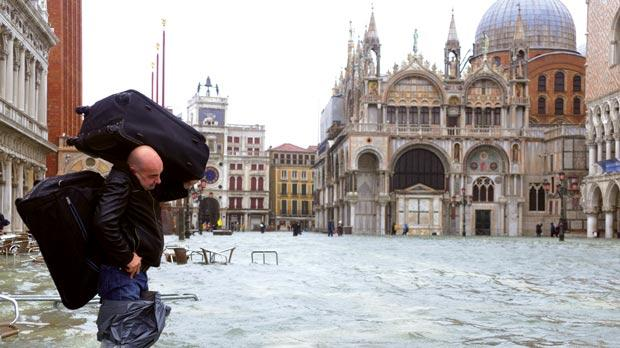 A man carries luggage on a flooded St Mark's square yesterday in Venice as rain and wind hit the north of Italy and the flooding reached 150 centimetres. Photo: AFP