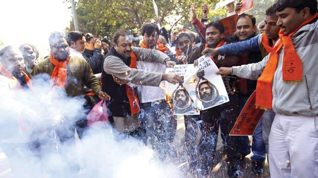 Hindu right-wing Bajrang Dal activists burn portraits of Kashmiri Mohammed Afzal Guru as they celebrate his execution in New Delhi, India, yesterday. Photo: PA
