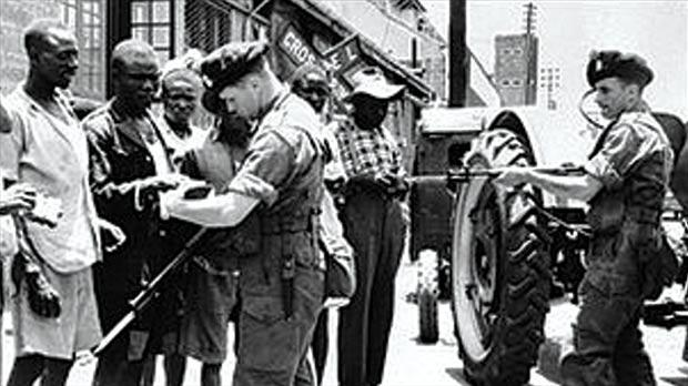 British soldiers checking identity papers of suspected Mau Mau rebels.