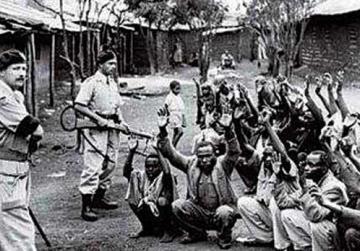 British soldiers guarding Mau Mau rebels.