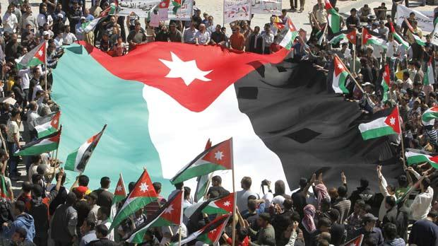 Jordanian protesters carrying a huge national flag during a demonstration in the capital Amman, yesterday demanding reforms and the ouster of the Prime Minister. Photo: AFP
