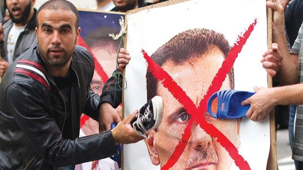 Protesters hitting a poster of Syria's President Bashar al-Assad with shoes during a demonstration outside the Syrian embassy in London. Photo: Leon Neal/AFP