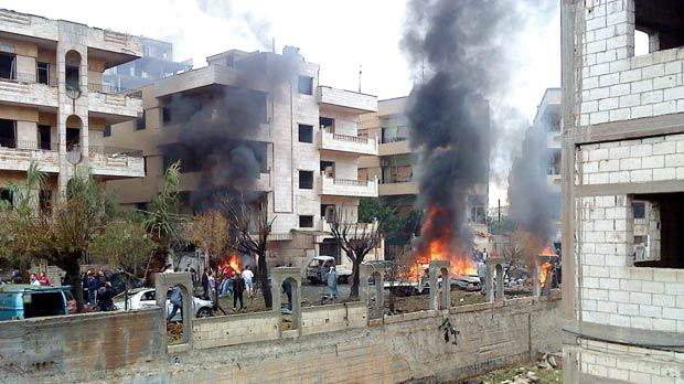 Damaged vehicles burn after what activists say was a bomb explosion at the Inshat area in Homs. Photo: Reuters