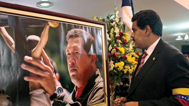 Venezuela's acting President Nicolas Maduro stands in front of a portrait of Venezuela's late President Hugo Chávez after a symbolic swearing-in ceremony in the presence of the flag-draped coffin of Chávez at the military academy where the funeral ceremony was held earlier in Caracas, Venezuela. Photo: PA
