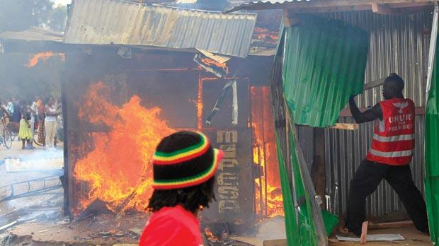A man wearing a reflective jacket with the inscription of Kenya's President elect Uhuru Kenyatta fights a fire at a residential area on the outskirts of capital Nairobi yesterday. Photo: Reuters