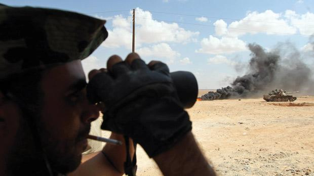 A Libyan National Transitional Council fighter looking through binoculars near the frontline in the outskirts of Bani Walid yesterday. Photo: AFP