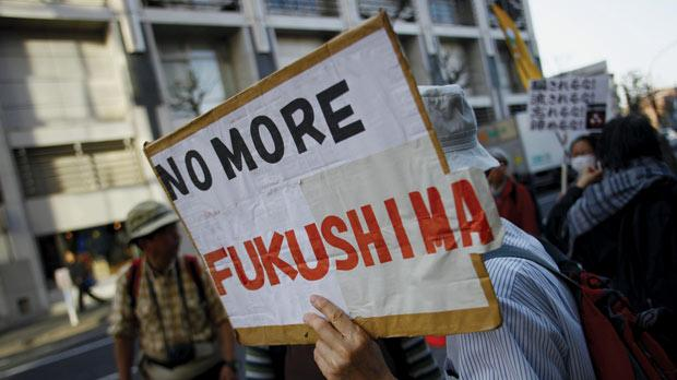 A protester holds a placard during an anti-nuclear demonstration in Tokyo, yesterday. Photo: PA