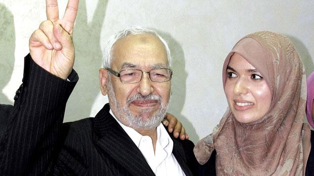 Tunisian leader and founder of the moderate Islamist party Ennahda, Rached Ghannouchi, flashing a V sign as he celebrates their electoral victory with his daughter, Intissar Kherigi, at the party's headquarters in Tunis. Photo: Amine Landoulsi/PA Wire