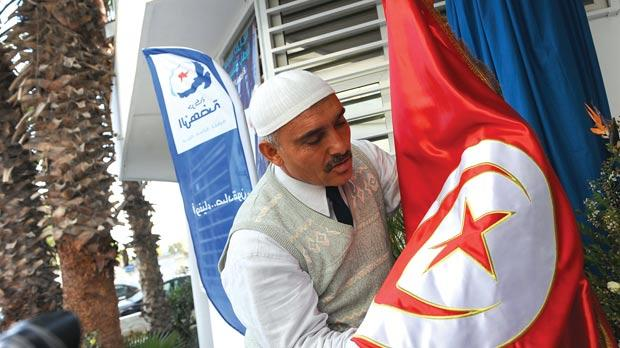 A supporter of Tunisia's Islamist Ennahda party embracing the national flag at the movement headquarters in Tunis. Photo: Fethi Belaid/AFP
