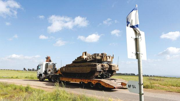 An Israeli tank is transported on a truck to the Israeli Syrian border in the Israeli-occupied Golan Heights. Photo: Reuters