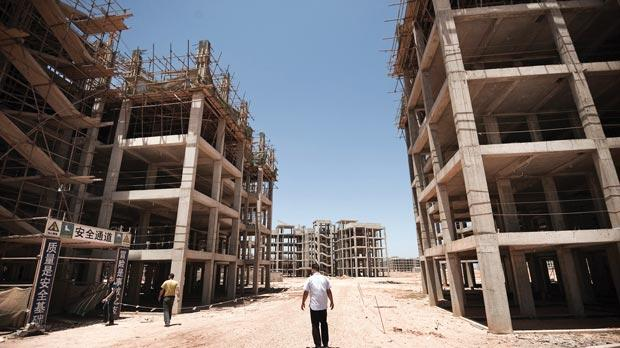 People walking past the abandoned construction site of the New Benghazi project in the Libyan rebel stronghold of Benghazi. Photo: Gianluigi Guercia/AFP