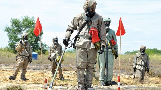 Soldiers in protective gear at a presentation on dectecting un­exploded ordnance and defoliant Agent Orange during the launch of a US-funded project to clean up the contamination.